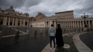 Two people stand in an empty St.Peter's Square, at the Vatican, as Pope Francis recites the Angelus noon prayer in his studio Friday, Jan. 1, 2021. (AP Photo/Alessandra Tarantino)
