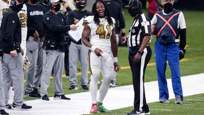 New Orleans Saints running back Alvin Kamara (41) reacts on the sideline next to side judge Keith Washington (7), after scoring his sixth rushing touchdown of the game, tying an NFL record, in the second half of an NFL football game against the Minnesota Vikings in New Orleans, Friday, Dec. 25, 2020. (AP Photo/Butch Dill)