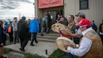 British Columbia Premier John Horgan (centre, blue jacket) is drummed into the Lower Post Residential School by Kaska drummers in Lower Post, B.C. on Orange Shirt Day in a 2019 handout photo (THE CANADIAN PRESS/HO-Manu Keggenhoff ).