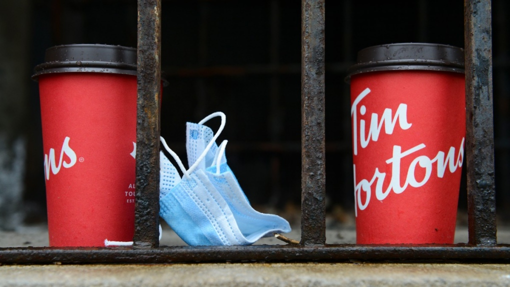 A used surgical face mask and Tim Hortons cups