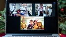 "Neighbours and friends Valerie Gapp, top right, and Lani Sommers, bottom right, play a game of virtual charades with their families, both in Ottawa, seen through a video call on Christmas Day, Friday, Dec. 25, 2020. Both families would normally spend the holiday hosting parties with neighbours or visiting with family from out of town. ""It's different this year but I do like getting to spend more time with my own children and starting new traditions, like our cross-Canada bingo planned for New Year's Eve. Different doesn't have to be bad; we always find a way to have fun and be together, even when we have to be physically apart,"" said Sommers. (Justin Tang/THE CANADIAN PRESS)"