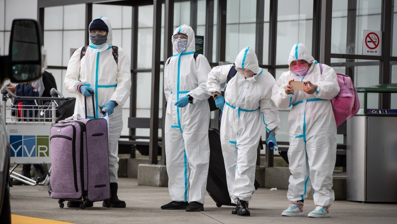People wearing protective face masks, goggles and Tyvek suits who said they traveled from Colombia wait for a car rental company shuttle, after arriving at Vancouver International Airport in Richmond, B.C., on Thursday, December 31, 2020. (THE CANADIAN PRESS/Darryl Dyck)