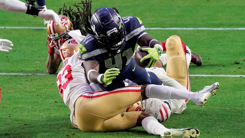 Seattle Seahawks running back Alex Collins scores a touchdown as San Francisco 49ers defensive back Tarvarius Moore (33) defends during the second half of an NFL football game, Sunday, Jan. 3, 2021, in Glendale, Ariz. (AP / Ross D. Franklin)