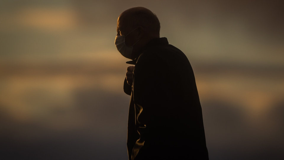 A man wearing a face mask to curb the spread of COVID-19 is silhouetted while walking on Ambleside Pier at sunset, in West Vancouver on Sunday, Jan. 3, 2021. (Darryl Dyck / THE CANADIAN PRESS)