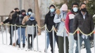 People wear face masks as they wait to be tested for COVID-19 at a clinic in Montreal, Sunday, January 3, 2021, as the COVID-19 pandemic continues in Canada and around the world. THE CANADIAN PRESS/Graham Hughes