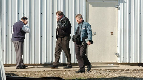 In this Oct. 19, 2009 photo, officials are seen during a search of a farm in Kinsman, Ill., which federal authorities say was owned by Tahawwur Hussain Rana, of Chicago. (AP / The Herald News, Liz Wilkinson Allen)