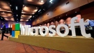 File-This Nov. 30, 2016, file photo shows a man walking past a Microsoft sign at the annual Microsoft shareholders meeting in Bellevue, Wash.(AP Photo/Elaine Thompson, File)