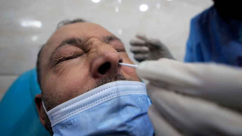 A nurse administers a PCR COVID-19 test on a man, Sunday, Dec.6, 2020 in a private laboratory of Algiers. (AP Photo/Fateh Guidoum)