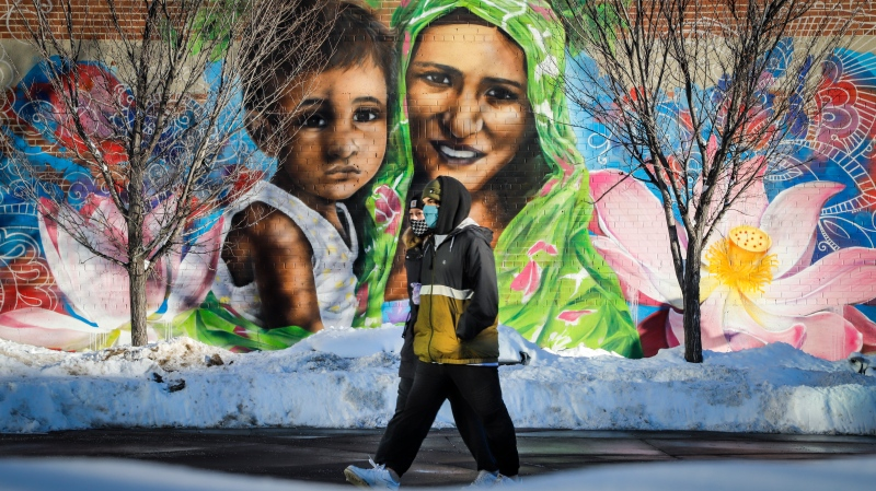A couple wearing masks walk past a mural of a mother and child in Calgary, Alta., Monday, Dec. 28, 2020, amid a worldwide COVID-19 pandemic. THE CANADIAN PRESS/Jeff McIntosh