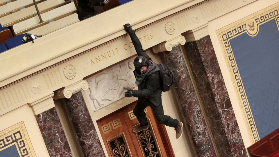 A protester is seen hanging