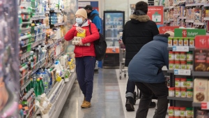 People wear face masks as they shop in a pharmacy in Montreal, Sunday, January 3, 2021, as the COVID-19 pandemic continues in Canada and around the world. THE CANADIAN PRESS/Graham Hughes