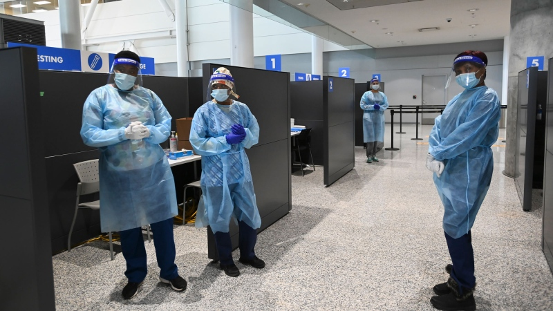 Health-care workers wait at COVID-19 testing stations located at the international arrivals area at Pearson International Airport in Toronto on Wednesday, January 6, 2021. THE CANADIAN PRESS/Nathan Denette