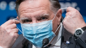 Quebec Premier Francois Legault removes his mask as he arrives at a news conference in Montreal, on Wednesday, January 6, 2021. THE CANADIAN PRESS/Paul Chiasson