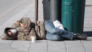 A homeless man wears a face mask as he sleeps on a street in Montreal, Monday, October 12, 2020, as the COVID-19 pandemic continues in Canada and around the world. THE CANADIAN PRESS/Graham Hughes