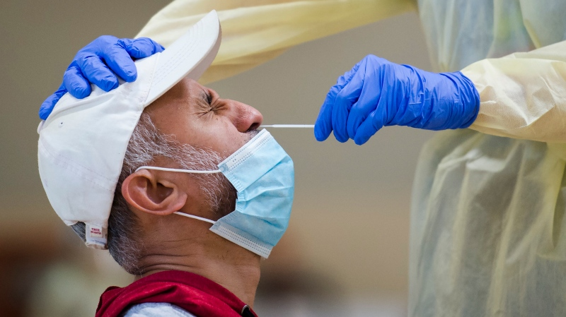 A man is tested for COVID-19 from a health-care worker at a pop-up testing centre at the Islamic Institute of Toronto during the COVID-19 pandemic in Toronto on Friday, May 29, 2020. (THE CANADIAN PRESS / Nathan Denette)