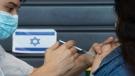 An Israeli receives a coronavirus vaccine from medical staff at a COVID-19 vaccination center in Tel Aviv, Israel, Wednesday, Jan. 6, 2021. (AP Photo/Sebastian Scheiner)