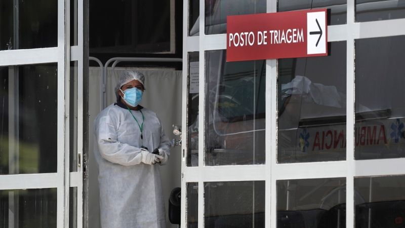 A health worker stands at the entrance of the HRAN Hospital that specializes in the care of new coronavirus cases, after a new patient arrived in Brasilia, Brazil, Thursday, Jan. 7, 2021. (AP Photo/Eraldo Peres)