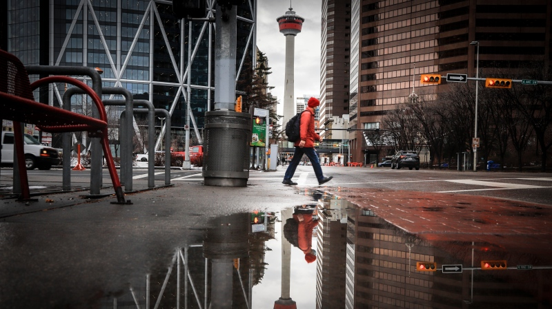 A pedestrian wearing a mask walks through an empty downtown Calgary, Alta., Wednesday, Dec. 9, 2020. THE CANADIAN PRESS/Jeff McIntosh