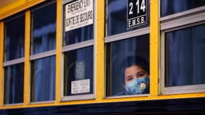 A student peers through the window of a school bus as he arrives at the Bancroft Elementary School in Montreal, on August 31, 2020. THE CANADIAN PRESS/Paul Chiasson
