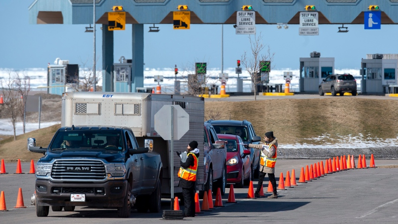 Provincial health department workers stop traffic that has crossed the Confederation Bridge in Borden-Carleton, P.E.I. on Sunday, March 22, 2020. THE CANADIAN PRESS/Andrew Vaughan
