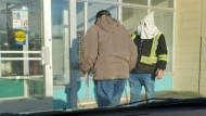 A man is seen outside a Grimshaw, Alta. store wearing a white hood (Supplied)