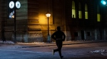 A man jogs along a street prior to a curfew in Montreal, Saturday, January 9, 2021, as the COVID-19 pandemic continues in Canada and around the world. The Quebec government has imposed a curfew to help stop the spread of COVID-19 starting at 8 p.m until 5 a.m. THE CANADIAN PRESS/Graham Hughes