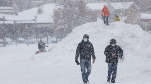 People walk through the snow in the village of Blue Mountain Ski Resort in The Blue Mountains, Ont., on the first day of a provincial lockdown Saturday, Dec. 26, 2020. THE CANADIAN PRESS/Cole Burston