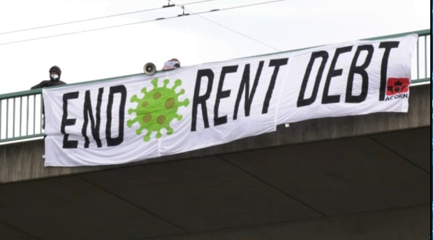 "A banner drop on the Cambie Bridge in Vancouver on Jan. 9, 2021 that reads ""End rent debt."""