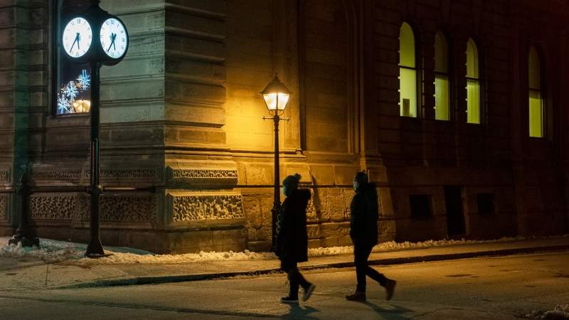People wear face masks as they walk along a street prior to a curfew in Montreal, Saturday, January 9, 2021, as the COVID-19 pandemic continues in Canada and around the world. The Quebec government has imposed a curfew to help stop the spread of COVID-19 starting at 8 p.m until 5 a.m. THE CANADIAN PRESS/Graham Hughes
