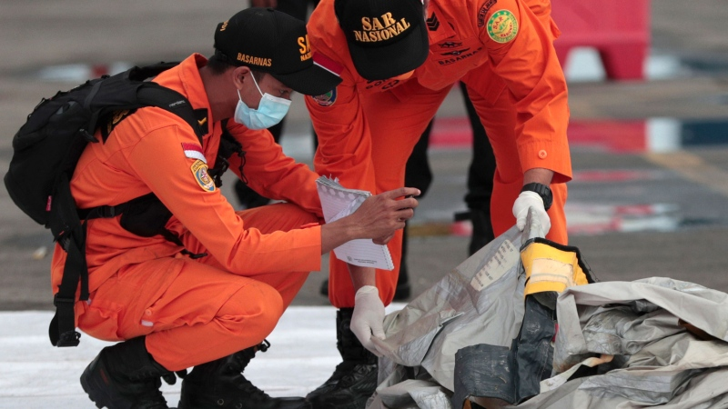 Rescuers inspects debris found in the waters around the location where a Sriwijaya Air passenger jet has lost contact with air traffic controllers shortly after take off, at the search and rescue command center at Tanjung Priok Port in Jakarta, Indonesia, Sunday, Jan. 10, 2021. The Boeing 737-500 took off from Jakarta for Pontianak, the capital of West Kalimantan province on Indonesia's Borneo island, and lost contact with the control tower a few moments later. (AP Photo/Dita Alangkara)