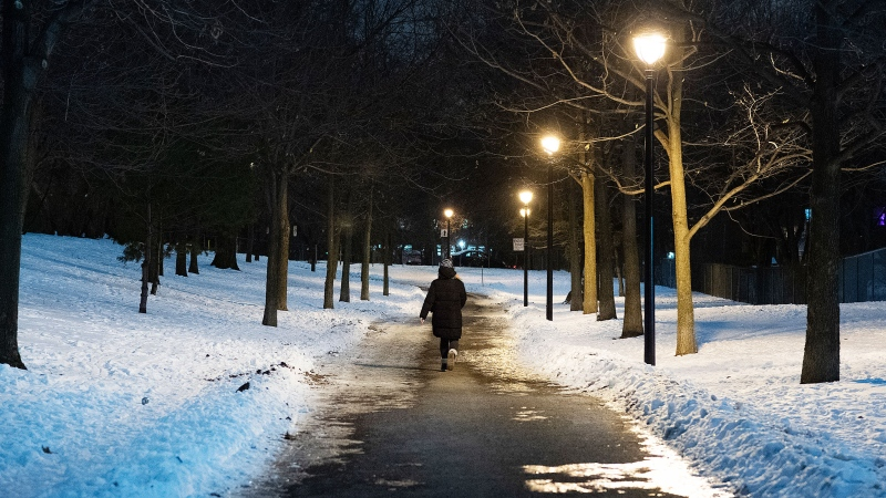A woman walks in a park shortly before a curfew comes into effect in Montreal, Sunday, January 10, 2021, as the COVID-19 pandemic continues in Canada and around the world. The Quebec government has imposed a lockdown and a curfew to help stop the spread of COVID-19. The curfew begins at 8 p.m until 5 a.m and lasting until February 8. THE CANADIAN PRESS/Graham Hughes