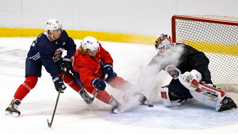 Florida Panthers goalie Chris Driedger (60) and Panthers defenseman Brady Keeper (25) defend the Goan from Panthers right wing Owen Tippett (74) during training camp in preparation for the 2021 NHL season Sunday, Jan. 10, 2021, in Sunrise, Fla. (David Santiago/Miami Herald via AP)