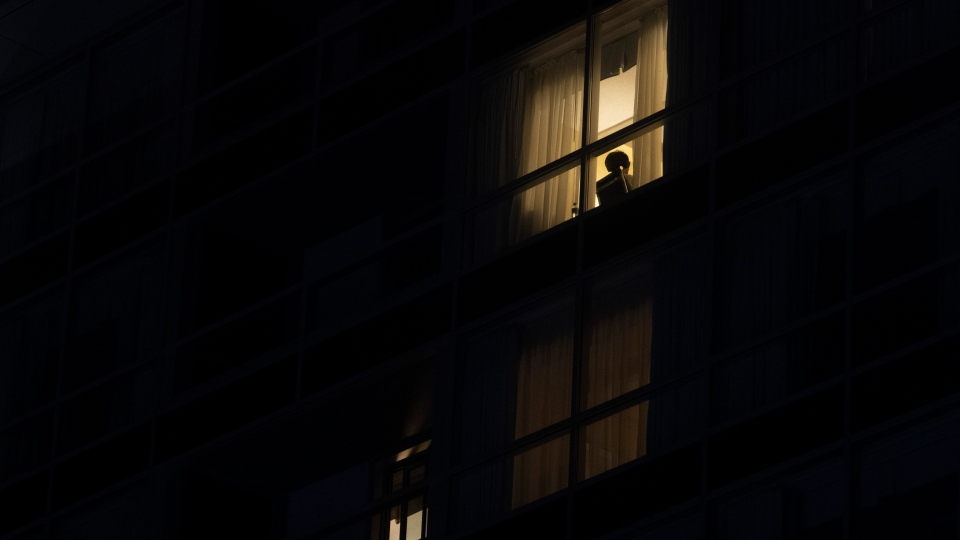 A person sits inside a building Saturday, Jan.  9, 2021 in Gatineau Que. The province implemented a curfew in efforts to reduce COVID-19 cases. (Adrian Wyld/THE CANADIAN PRESS)