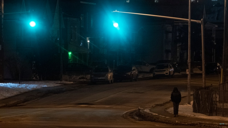 A man walks along a street in Gatineau, Que as a province wide curfew began on Saturday, January 9, 2021. (Adrian Wyld/THE CANADIAN PRESS)