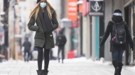A woman wears a face mask as she walks along a street in Montreal, Sunday, January 3, 2021, as the COVID-19 pandemic continues in Canada and around the world. THE CANADIAN PRESS/Graham Hughes