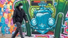 A man walks past a mural in Toronto on Monday January 11, 2021. THE CANADIAN PRESS/Frank Gunn