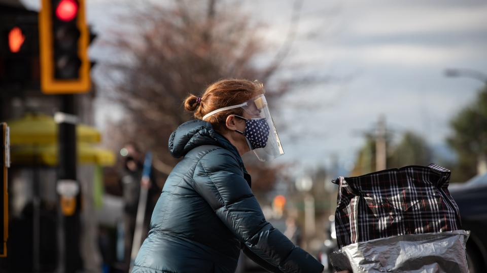 A woman wears a face mask and shield to curb the spread of COVID-19 while walking in North Vancouver, B.C., on Wednesday, January 6, 2020. (THE CANADIAN PRESS / Darryl Dyck)