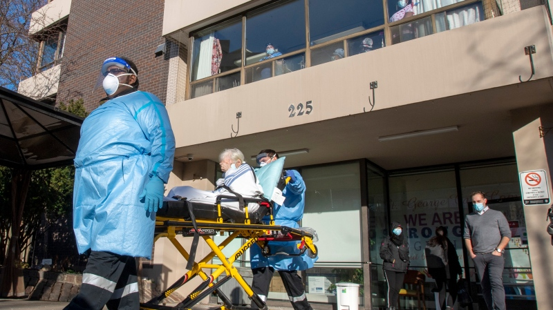 A resident is taken to a waiting ambulance as nurses and PSWs at Sienna Senior Living St. George Care Community in Toronto watch from the windows as a support rally takes place in front of the building on Thursday January 7, 2021. THE CANADIAN PRESS/Frank Gunn