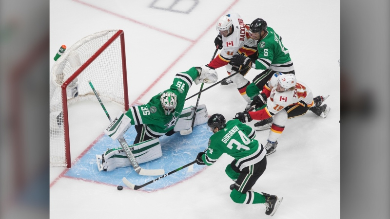Calgary Flames' Mikael Backlund (11) is stopped by Dallas Stars goalie Anton Khudobin (35) as Flames' Matthew Tkachuk (19), and Stars' Denis Gurianov (34) and Andrej Sekera (5) battle in front during the first period of a first round NHL Stanley Cup playoff hockey series in Edmonton, on Tuesday August 11, 2020. THE CANADIAN PRESS/Jason Franson