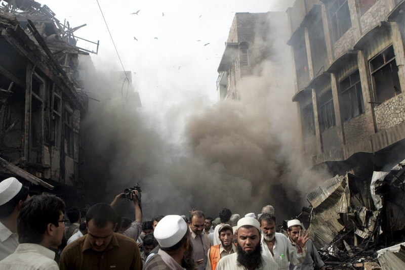 People gather at the site of a car bomb explosion at a market in Peshawar, Pakistan on Wednesday, Oct. 28, 2009. (AP / Mohammad Sajjad)