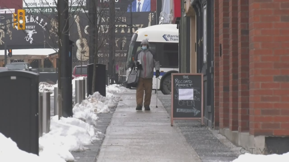 A man wearing a mask walks along the downtown streets in Barrie, Ont. on Tues., Jan. 12, 2021. (Rob Cooper/CTV News)