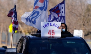 A man holds up a placard calling for the impeachment of U.S. President Donald Trump during a car rally through the streets of downtown Denver, Sunday, Jan. 10, 2021. (AP Photo/David Zalubowski)