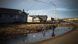 Indigenous children play in the water filled ditches in the northern Ontario First Nations reserve in Attawapiskat, Ont., on Tuesday, April 19, 2016. (THE CANADIAN PRESS/Nathan Denette)