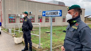 Finance police officers wearing face masks to curb the spread of COVID-19 stand guard during the first hearing of a maxi-trial against more than 300 defendants of the 'ndrangheta crime syndicate, outside a specially constructed bunker near the Calabrian town of Lamezia Terme, southern Italy, Wednesday, Jan. 13, 2021. (AP Photo/Andrea Rosa)