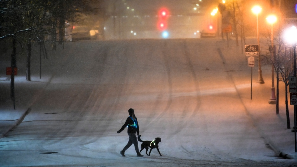 A dog walker crosses a street during Tuesday night's snow storm in downtown Minneapolis, Nov. 10, 2020. (Aaron Lavinsky/Star Tribune via AP)