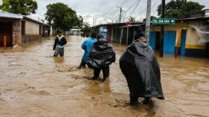 Top scientists warn of a 'ghastly future' for the planet as leaders underestimate ecological threats. Pictured here, people wade trough a flooded street in Honduras on November 18, 2020, following the passage of Hurricane Iota. (Wendell Escoto/AFP/Getty Images)