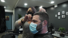 Natalie Klein, co-owner of Bladez 2 Fadez in Innisfail, Alta., cuts a client's hair in the shop on Jan. 12. On Jan. 13, the store announced on Facebook it was now a pet grooming salon in an attempt to contravene a public health order that mandated its closure.