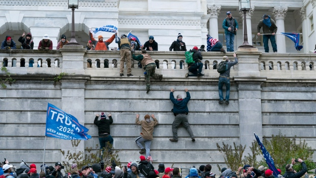 In this Jan. 6, 2021 file photo rioting supporters of U.S. President Donald Trump climb the west wall of the the U.S. Capitol in Washington. (AP Photo/Jose Luis Magana, File)
