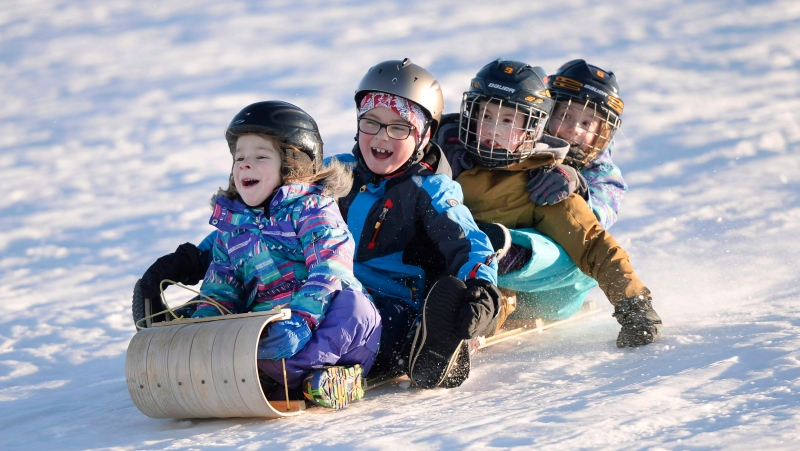 From left, Toby, 5, Caplan, 7, Mae, 8, and Claire, 8, toboggan at Mooney's Bay Park, in Ottawa on Christmas Day, Sunday, Dec. 25, 2016. THE CANADIAN PRESS/Justin Tang