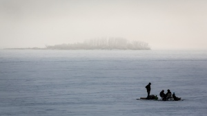 In this file photo, ice fishermen huddle over a hole in the ice on Ghost Lake Reservoir near Cochrane, Alta., Sunday, Dec. 27, 2020, amid a worldwide COVID-19 pandemic. THE CANADIAN PRESS/Jeff McIntosh